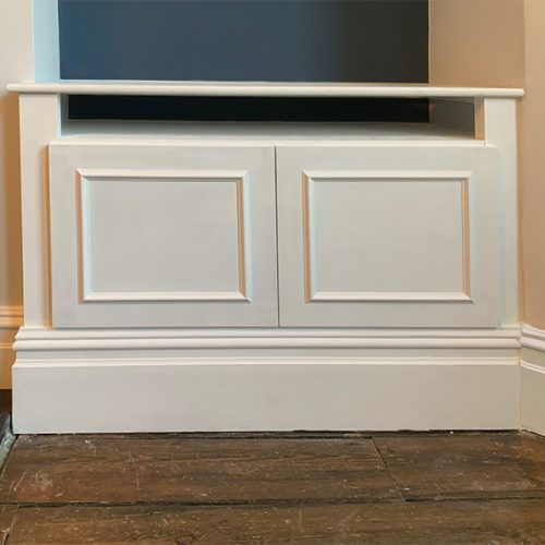 White media base unit with pronounced skirting board trim. Doors mounted on cabinet hinges. Image acts as a button to another example of the image.