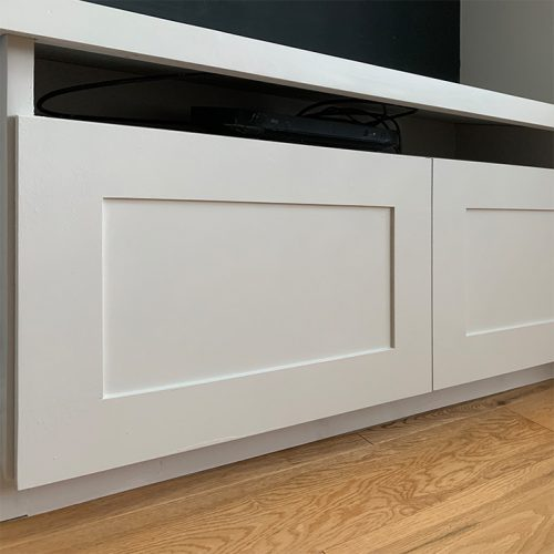 Contemporary media base unit with landscape shaker doors all in white. Image acts as a button to further images of the same project.